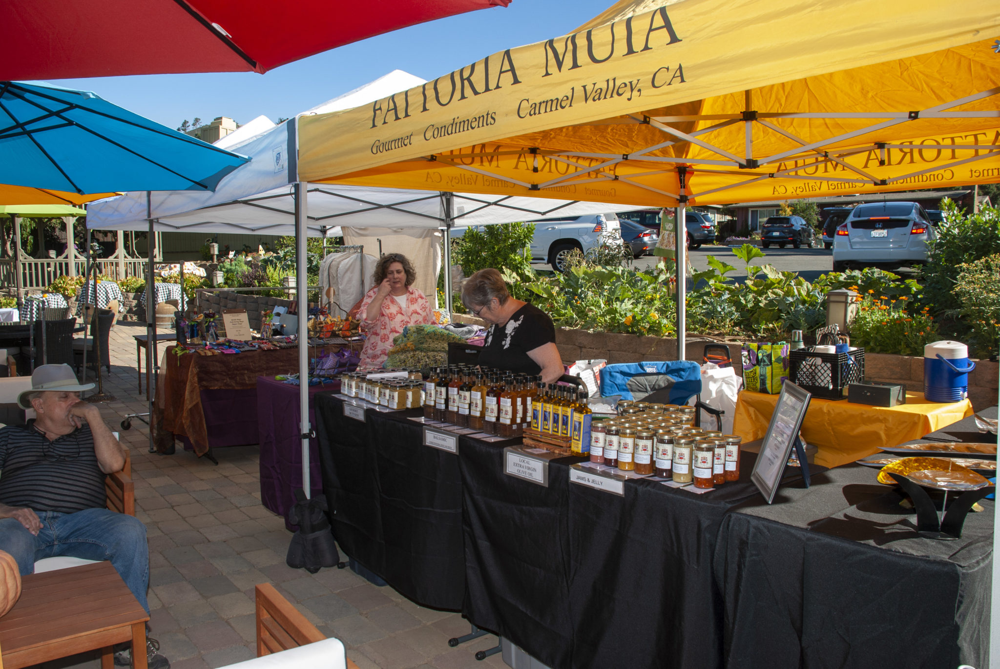 An outdoor table with food for sale - various jams/jellies - a bright yellow tent and two people working at the table.