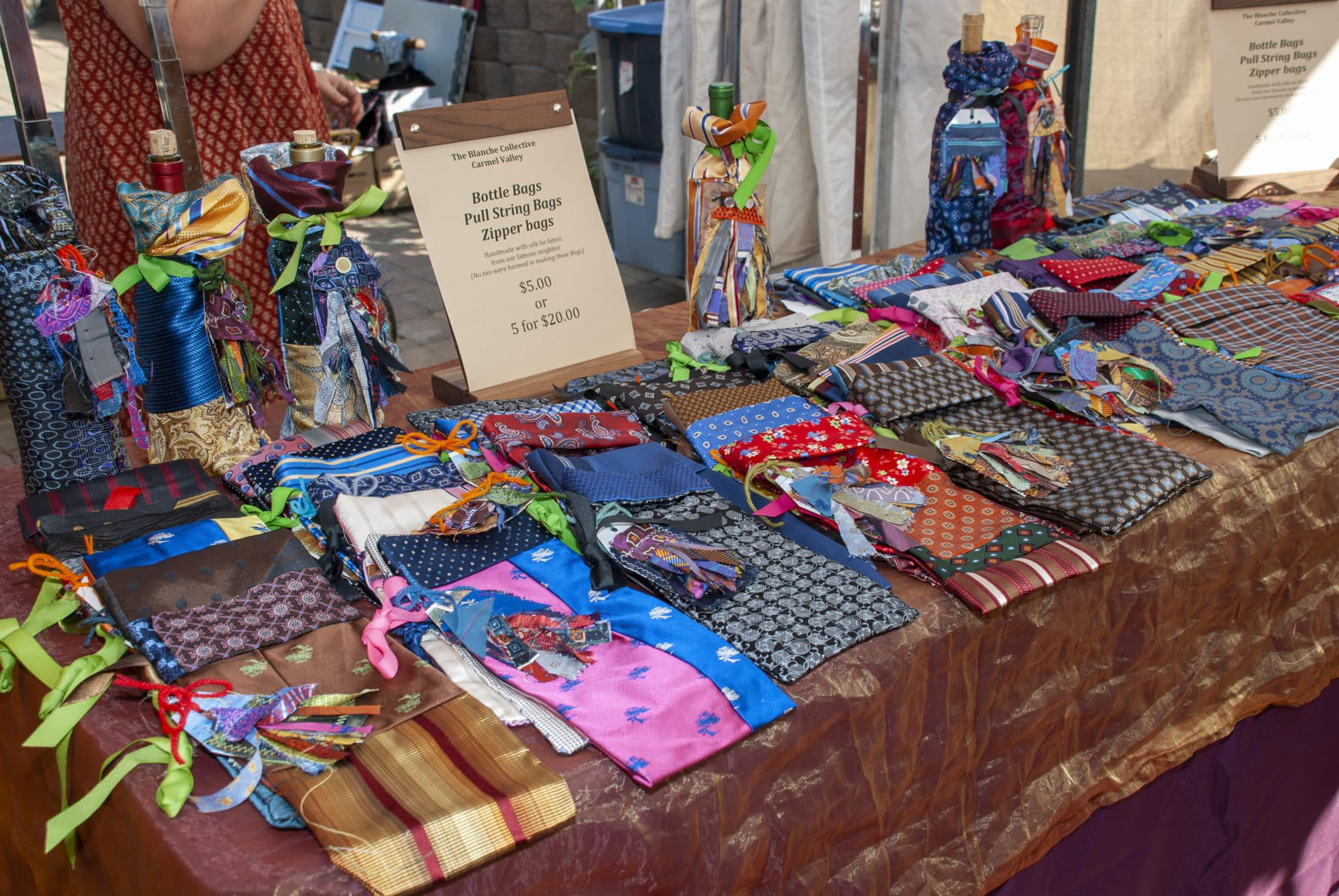 table with colorful fabric sewn into bags to hold bottles, as well as colorful pouches on the table.