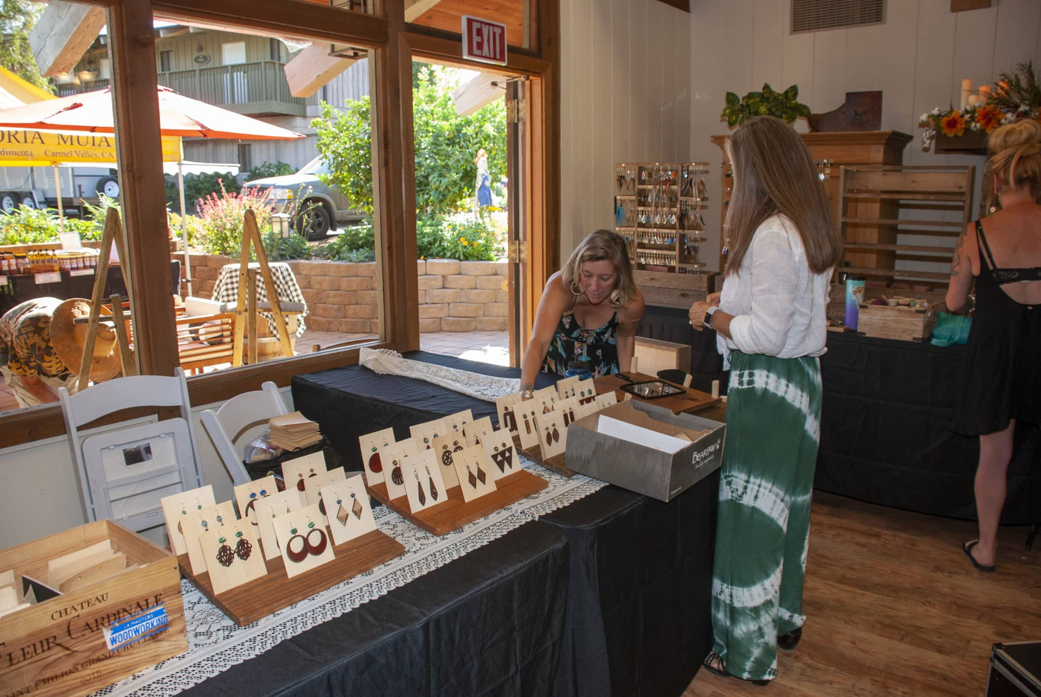 A table display with earrings on tan cardboard for sale in front of a large window and two women near the end of the table.