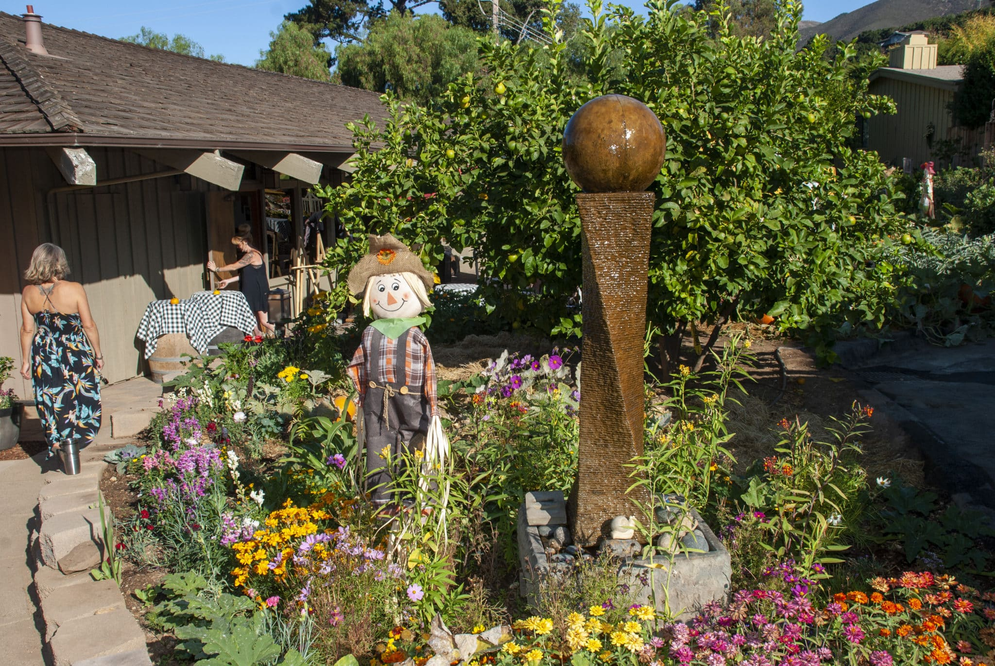 Yellow and orange flower bed with a brown scarecrow to the left and a brown iron sculpture with a ball on top that is a fountain.