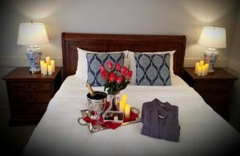 flowers, champagne, robes lying on bed