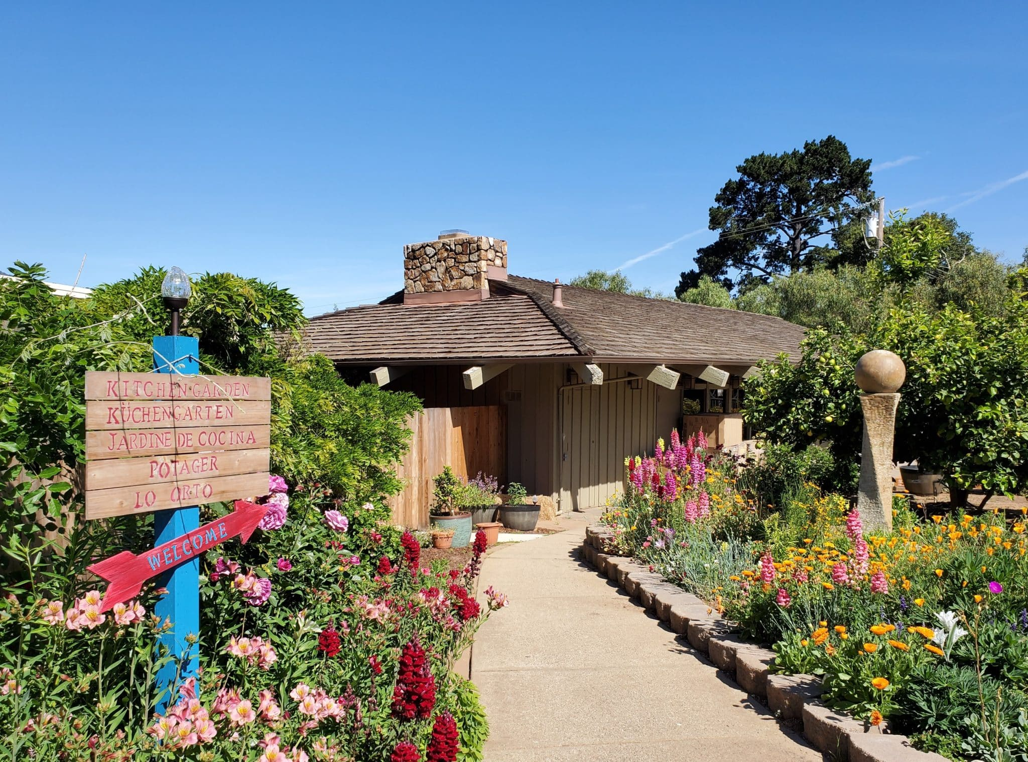 Exterior view of Carmel Valley Lodge cottage surrounded by colorful flowers, directional signs and blue skies
