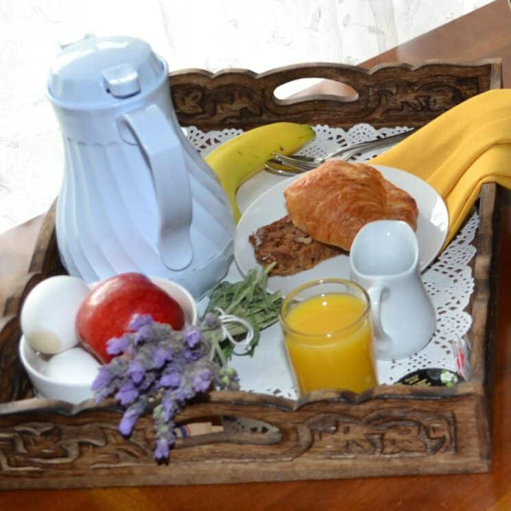 hand carved breakfast try with croissant, coffee, eggs, juice and fruit