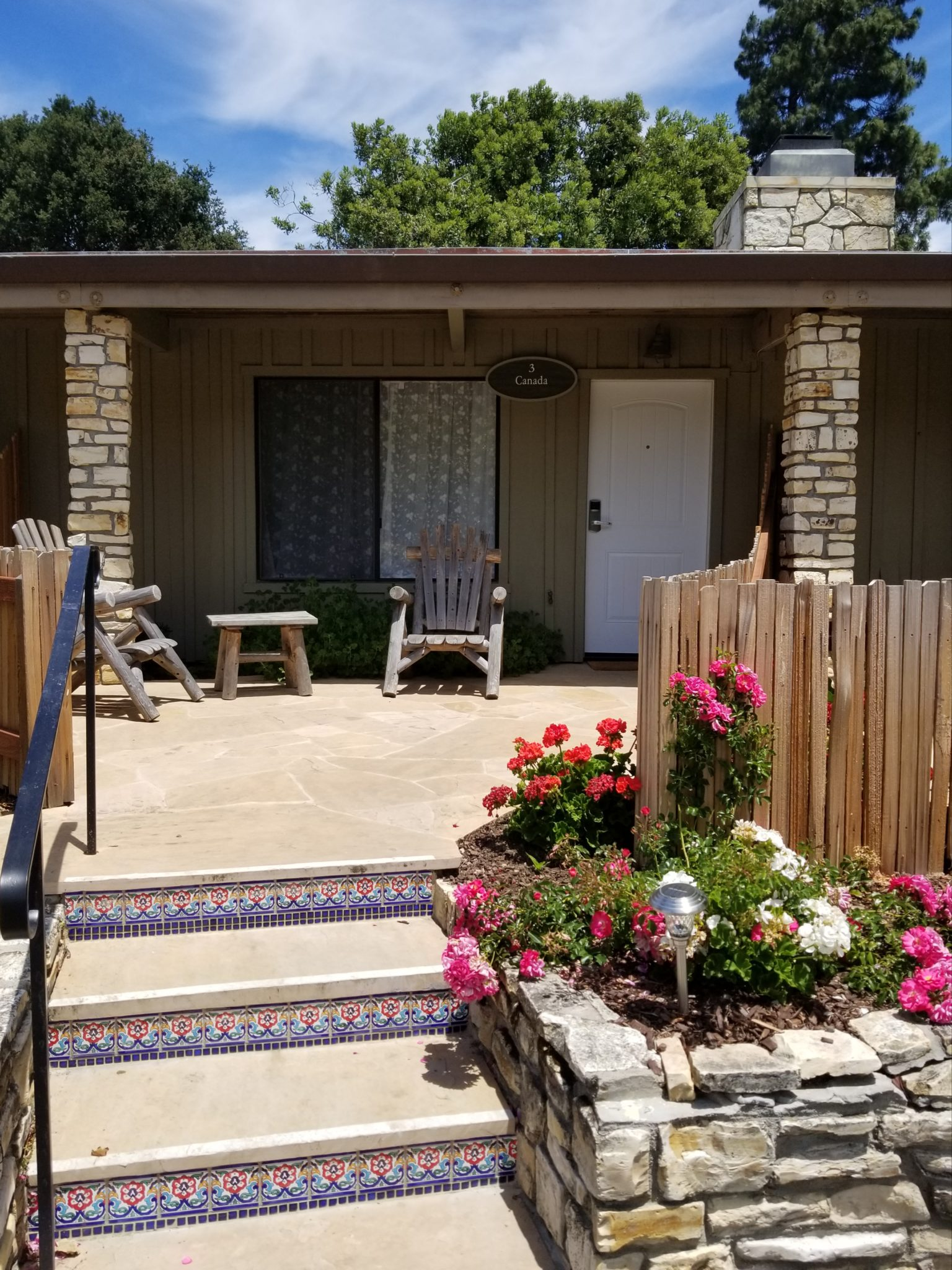 Guest room entrance with concrete steps, blooming colorful flowers and two chairs