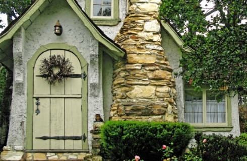 A fairytale-looking cottage with white exterior, light green door, green trim, and layered stone fireplace