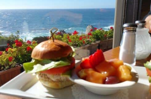 Tuna, tomato, and lettuce on Brioche bun with a side of fruit salad sitting on table with view of the ocean