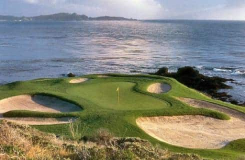 View of a hole on a golf course with multiple sand traps next to cliffs and the ocean