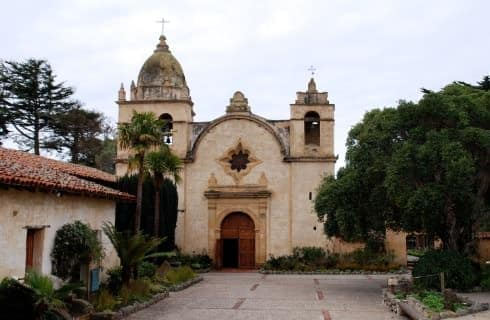 Old Spanish mission with light colored walls and red-tiled roof surrounded by paver driveway and lush green vegetation