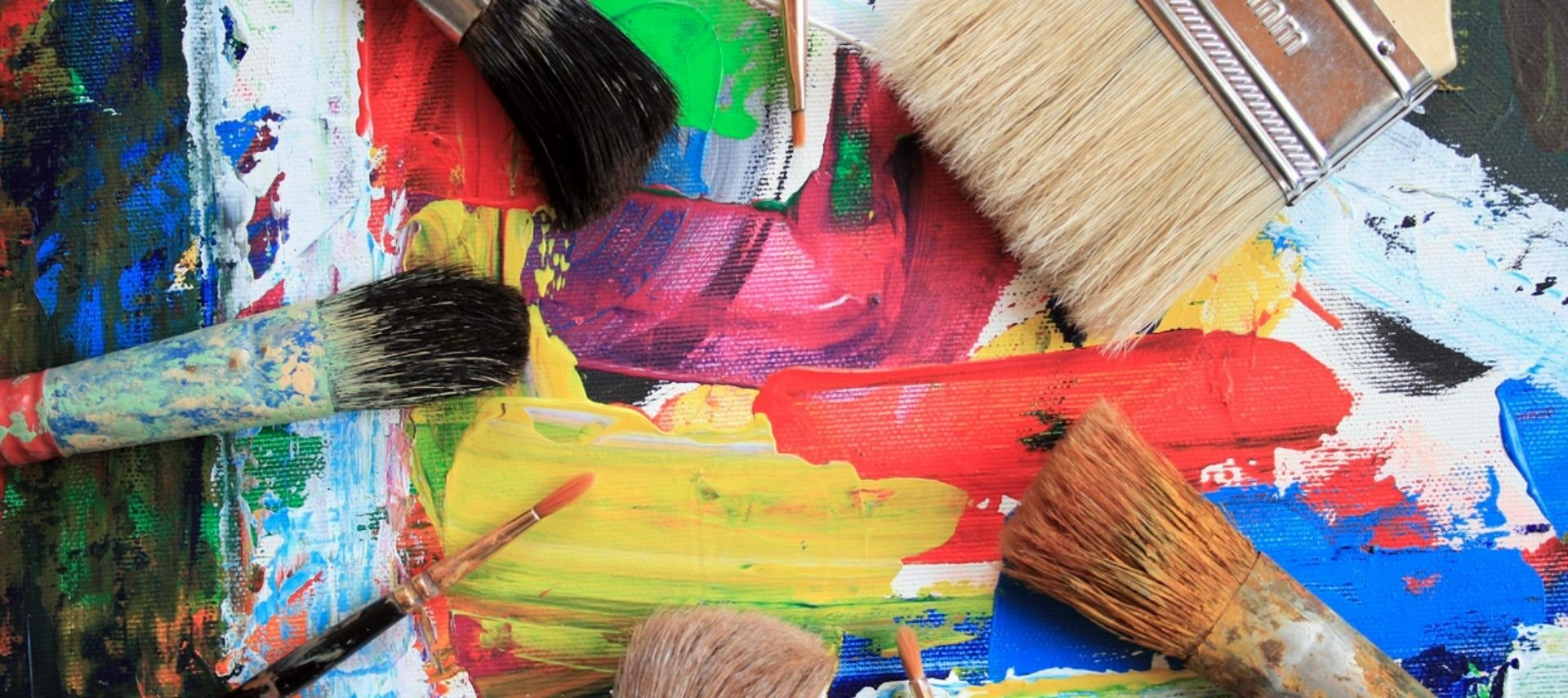 Brush marks in colorful paint with several different shaped paint brushes