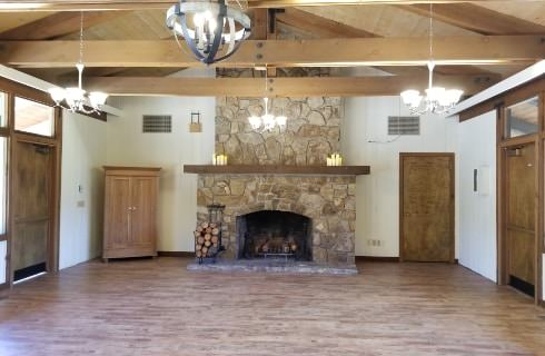 Large room for events with large stone fireplace and wood mantel