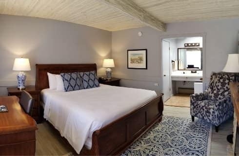 Bedroom with dark wood headboard and footbard with white bedding and dark wood nightstands with white and navy lamps