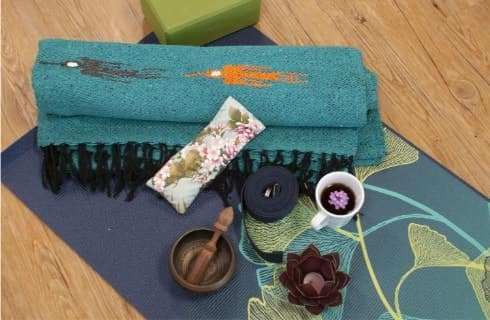 Blue and teal yoga mats with a bronze candle holder with tea light and white porcelain cup filled with tea
