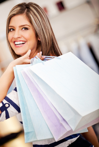 Woman with brown hair, smiling, looking over her shoulder carrying shopping bags