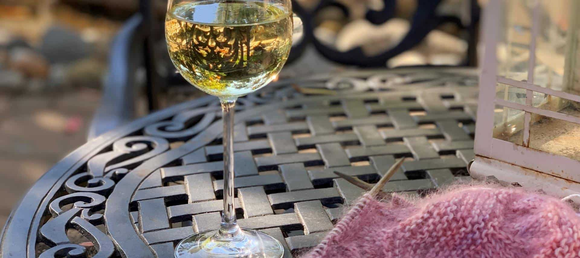 Wine glass with white wine sitting on rod iron patio table next to knitting needles and knitted pink scarf