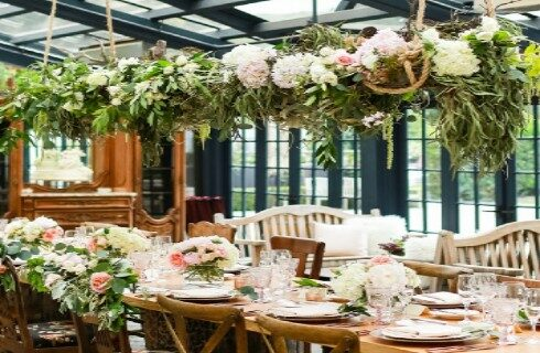 wedding tables set for lunch with flowers on table and hanging from ceiling