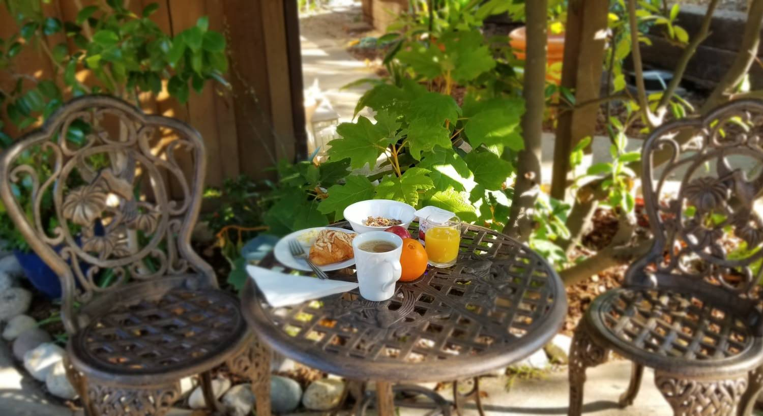 Small breakfast with a pastry, yogurt and granola, orange, apple, apple juice, and coffee in white porcelain dishes sitting on rod iron table on patio