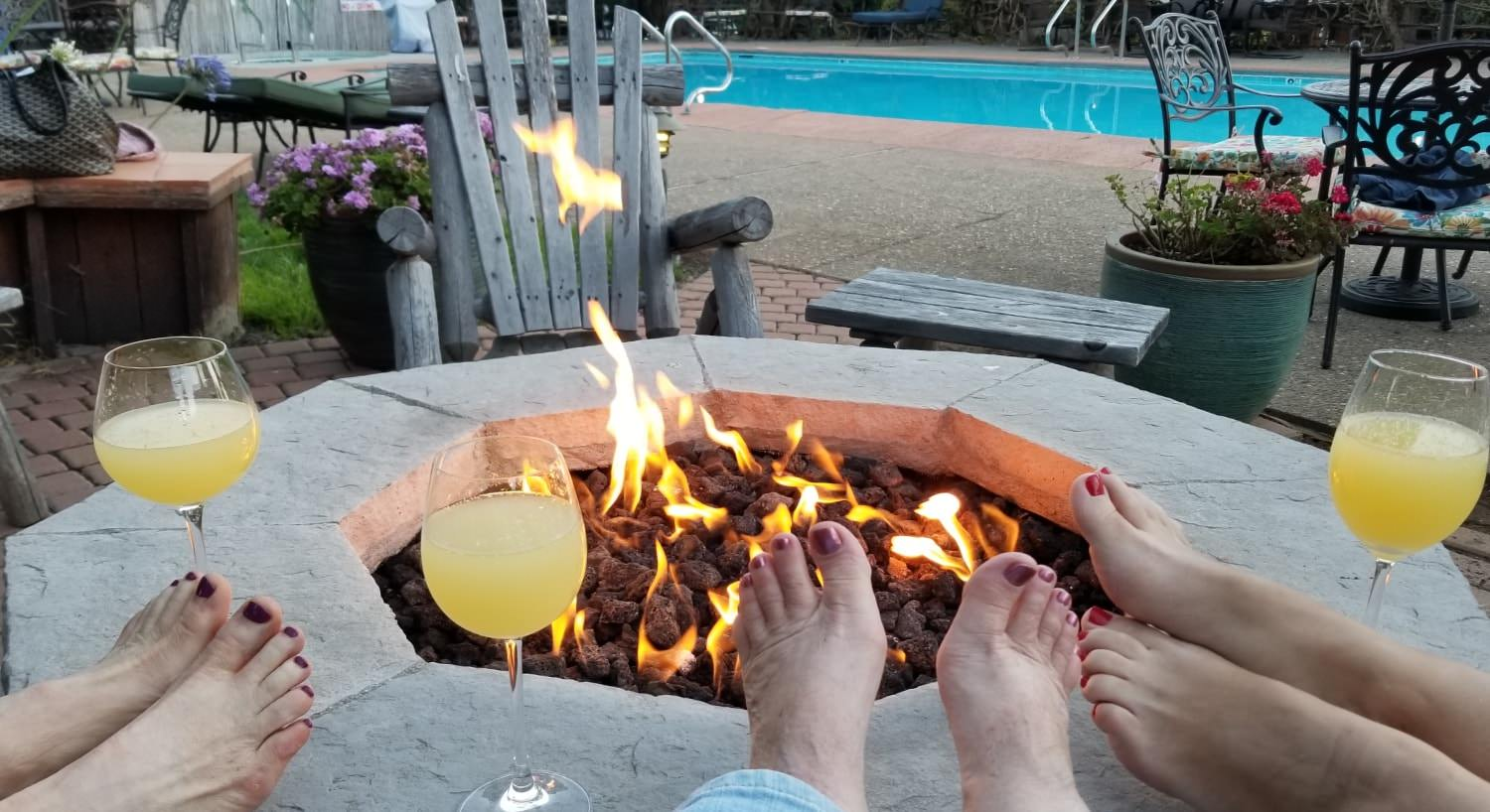 Three ladies feet with painted toe nails resting on firepit with wine glasses overlooking a fire near the pool