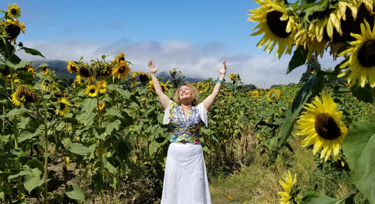 Woman with arms raised up and smiling in the sunshine in a field of large sunflowers