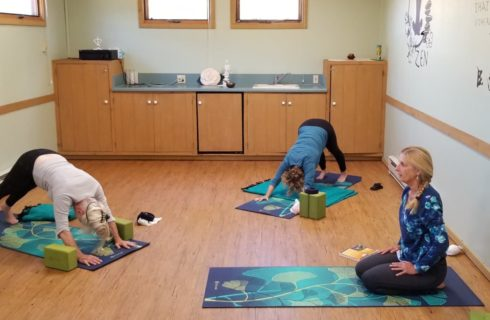 Three ladies in a yoga studio doing yoga poses on multicolored yoga mats