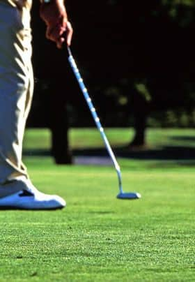 Golfer lining up to putt.