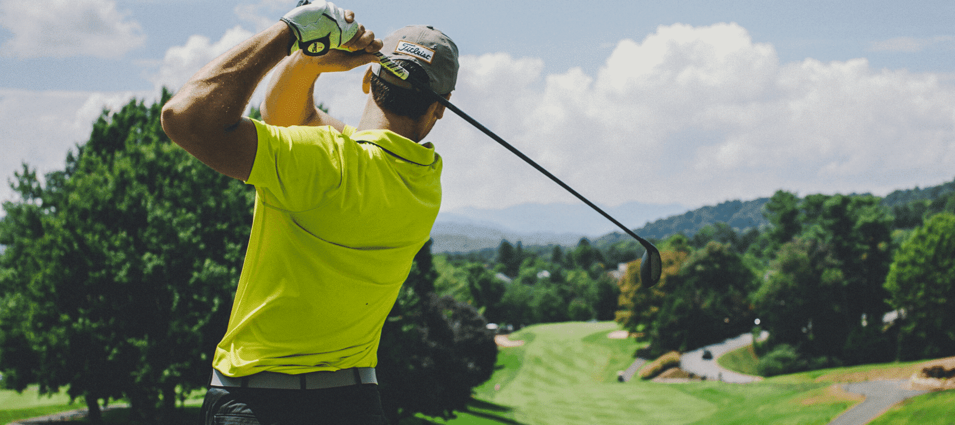 Man in yellow shirt playing golf on a sunny day.
