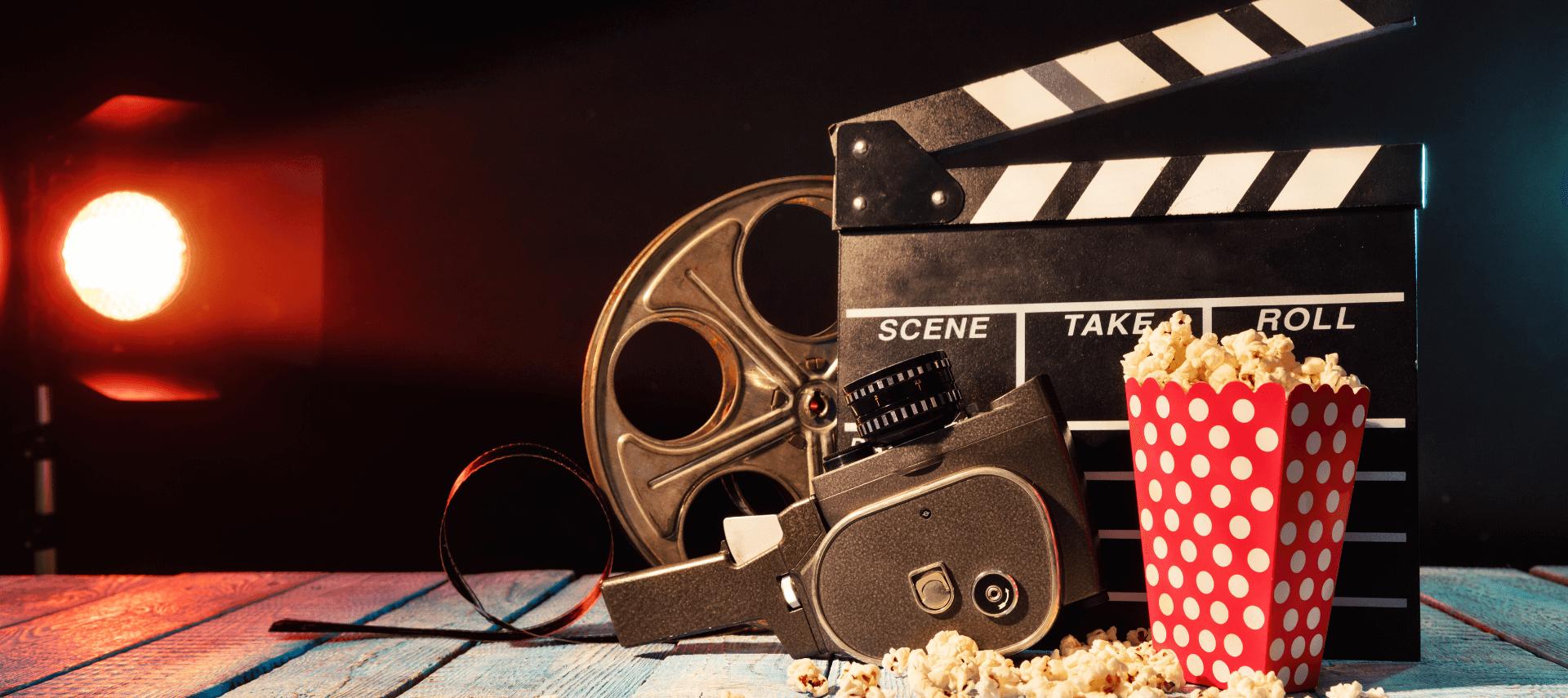 Film reel, popcorn, clapperboard, and lights