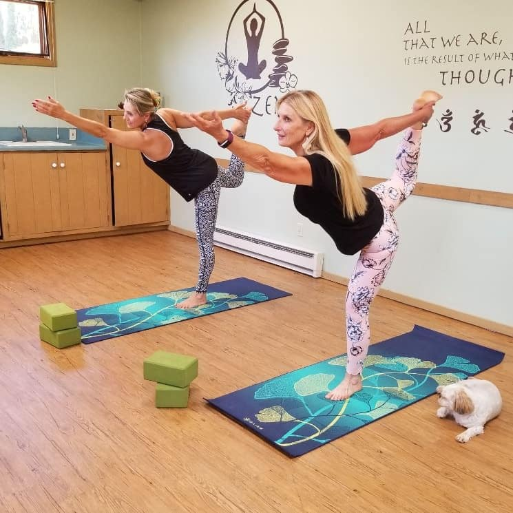 Two woman in a yoga pose standing on blue and teal yoga mats with small white and tan dog laying nearby