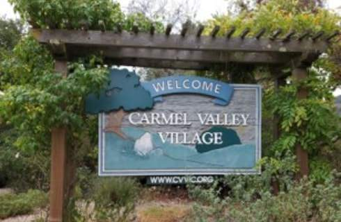 Wooden pergola with dark stain holding a Welcome to Carmel Valley Village sign surrounded by trees and bushes